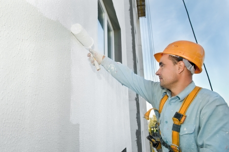7879988 - builder worker painting facade of building house with roller